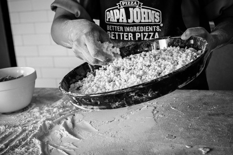 Cheese Being Added To A Deep Crust Pizza Base | Papa John's
